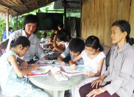 Bà Nguyễn Thị Mười và Họa sĩ Duy Bảo Việt tại lớp học vẽ miễn phí.