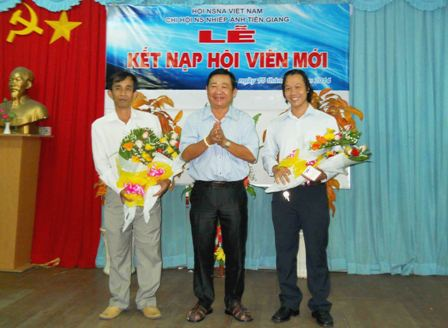 Soạn giả Huỳnh Anh (Chủ tịch Hội Văn học - Nghệ thuật tỉnh) tặng hoa chúc mừng cho hai hội viên mới