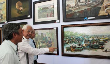 Họa sĩ Trần Khánh Chương, Chủ tịch hội Mỹ thuật Việt Nam (đứng giữa) thuyết trình về các tác phẩm tham gia triển lãm với đại biểu.