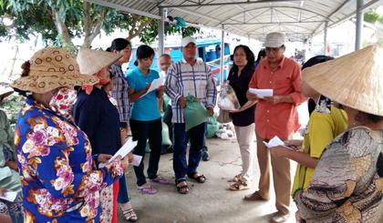 Anh Đỗ Hồng Trí (thứ 5 từ phải sang) trao quà cho các hộ nghèo, hộ khó khăn phường Tân Long, giúp bà con vui xuân, đón tết.